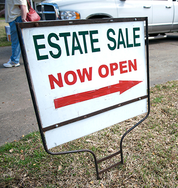 an estate sale yard sign guides customers to a local neighborhood sale