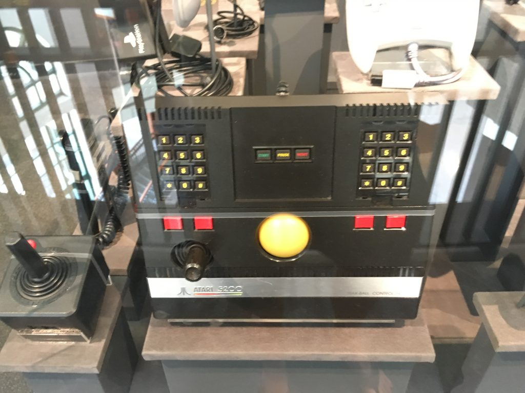 black video game console with yellow ball in center