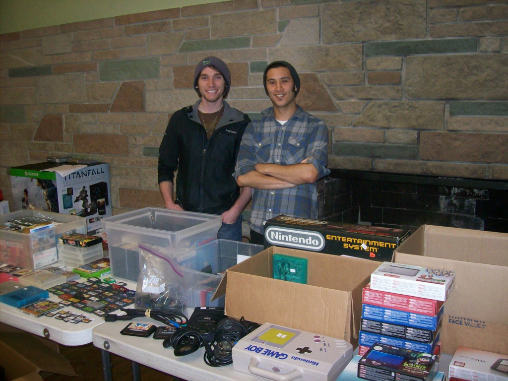 shot of two young men in stocking caps in front of tables filled with video games and cargridges