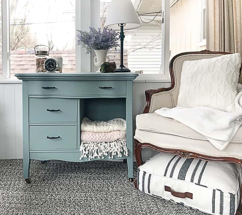 A blue dresser sits next to a white armchair.