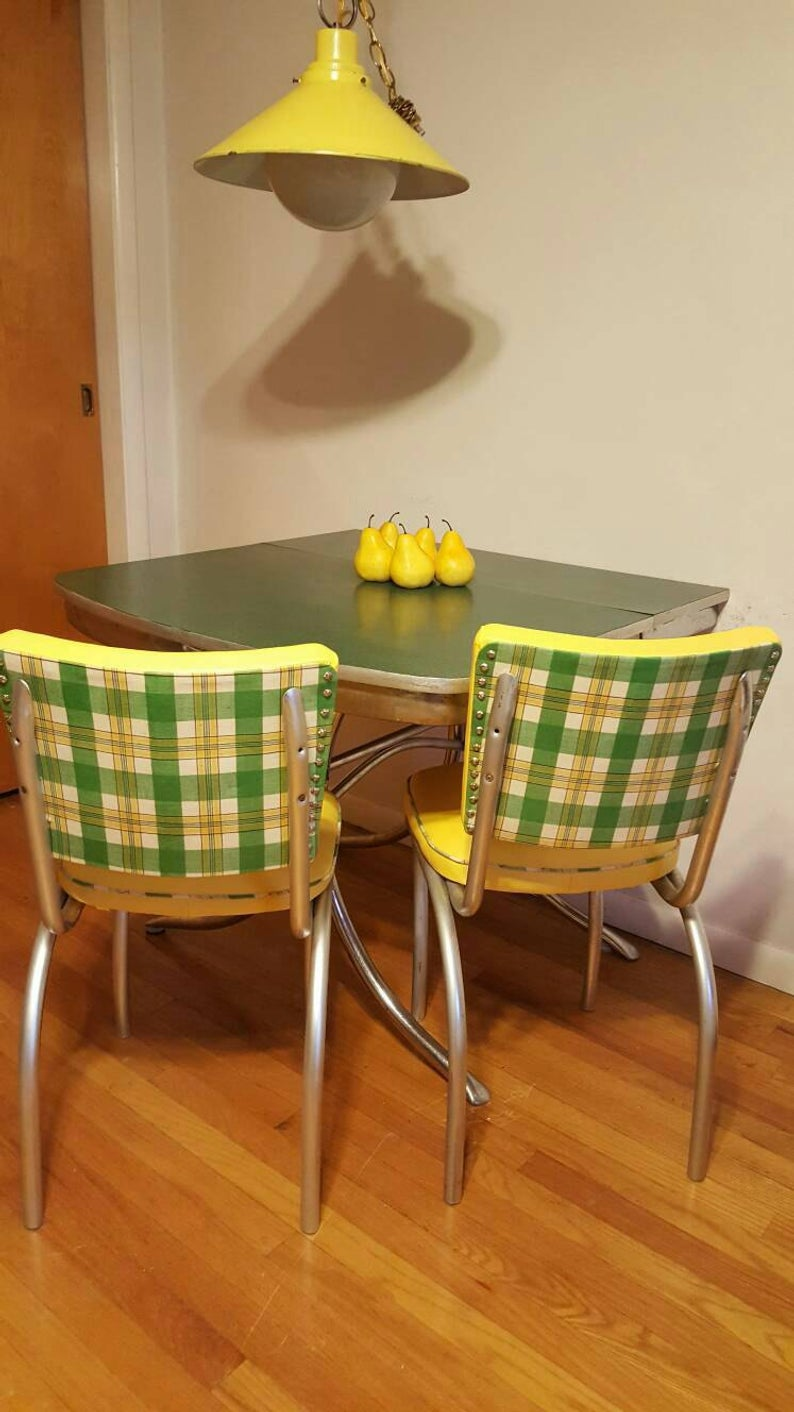 Yellow vinyal and green plaid chairs with table.