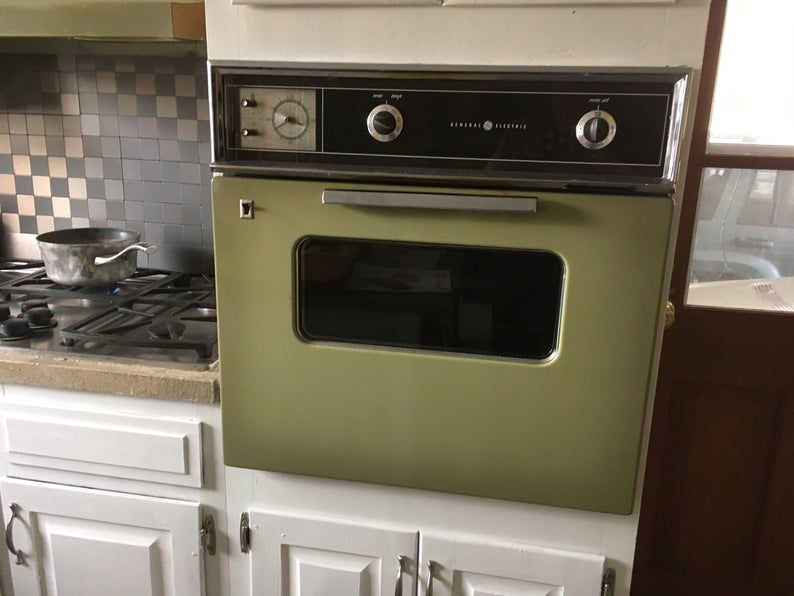 Avocado green wall oven surrounded by white cabinets.