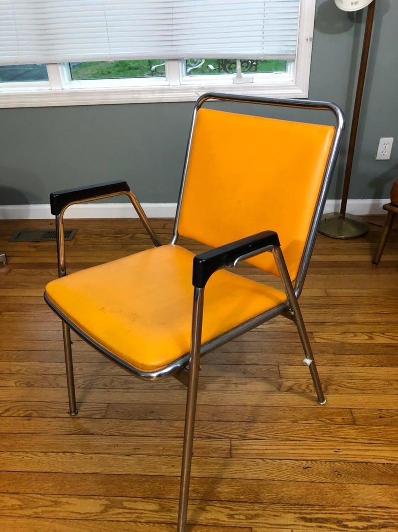 Orange chair with metal frame and black armrests.