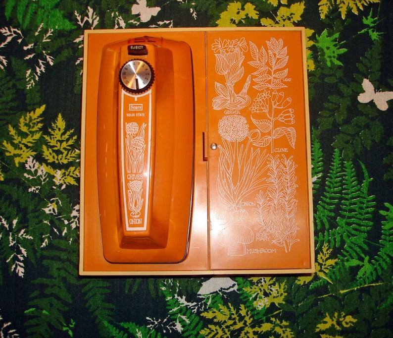 Orange hand mixer against green background.