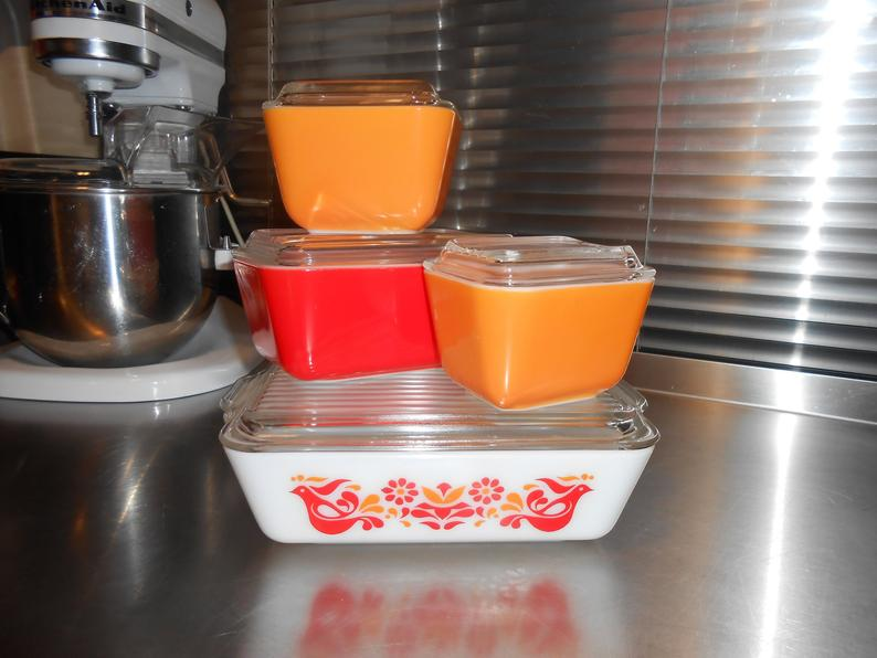 Four glass Pyrex dishes in orange and red.