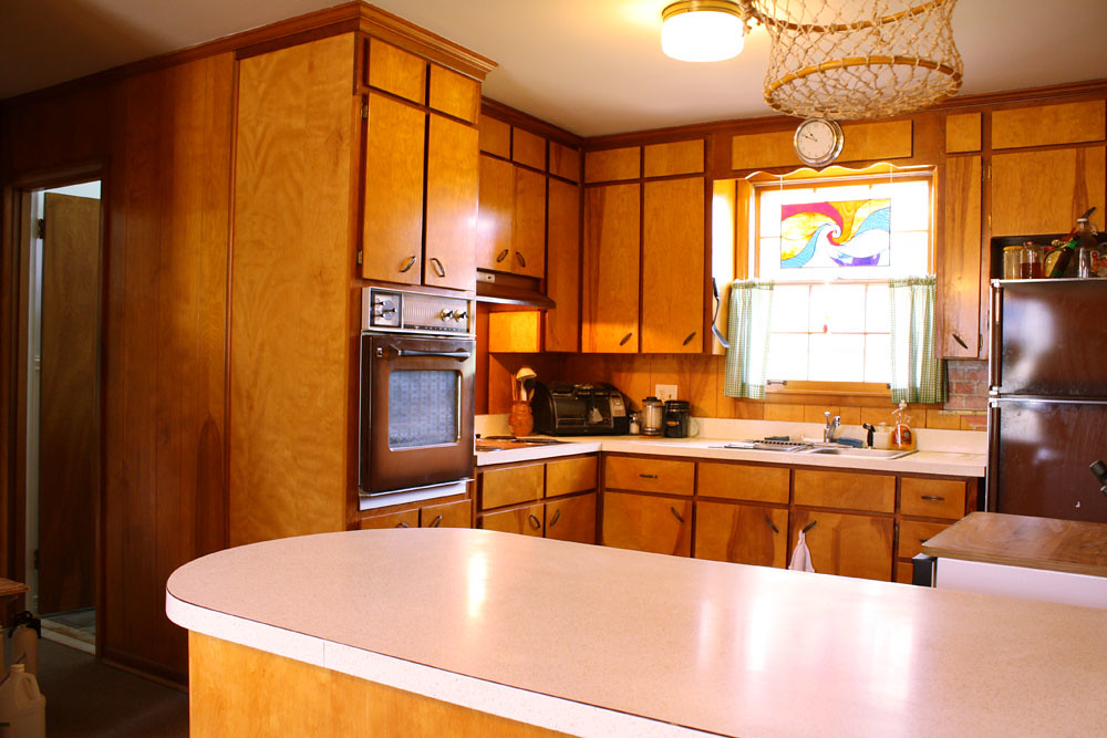 A 70s kitchen with brown cabinets and laminate counters.