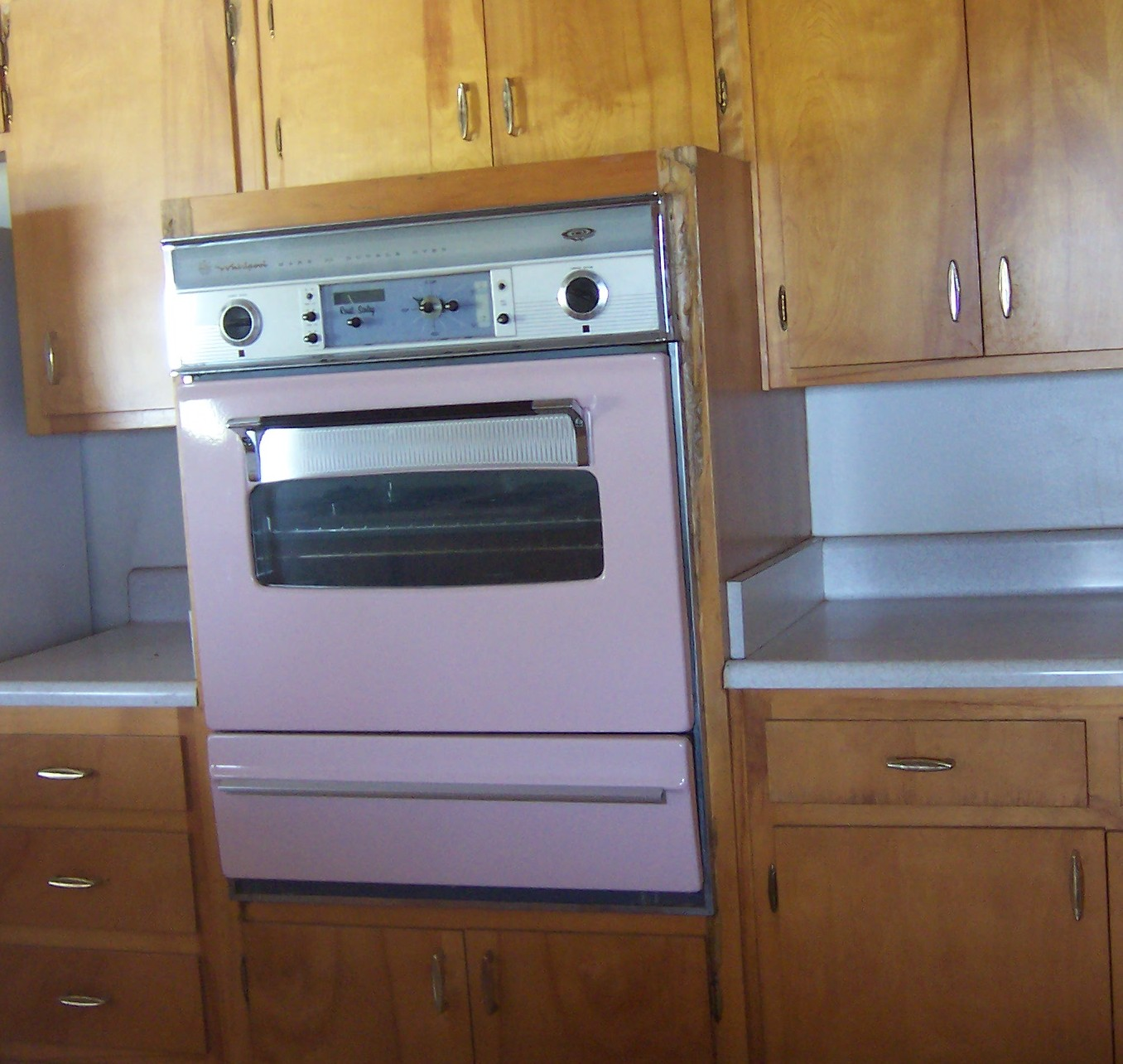 A pink wall oven in a wooden kitchen.