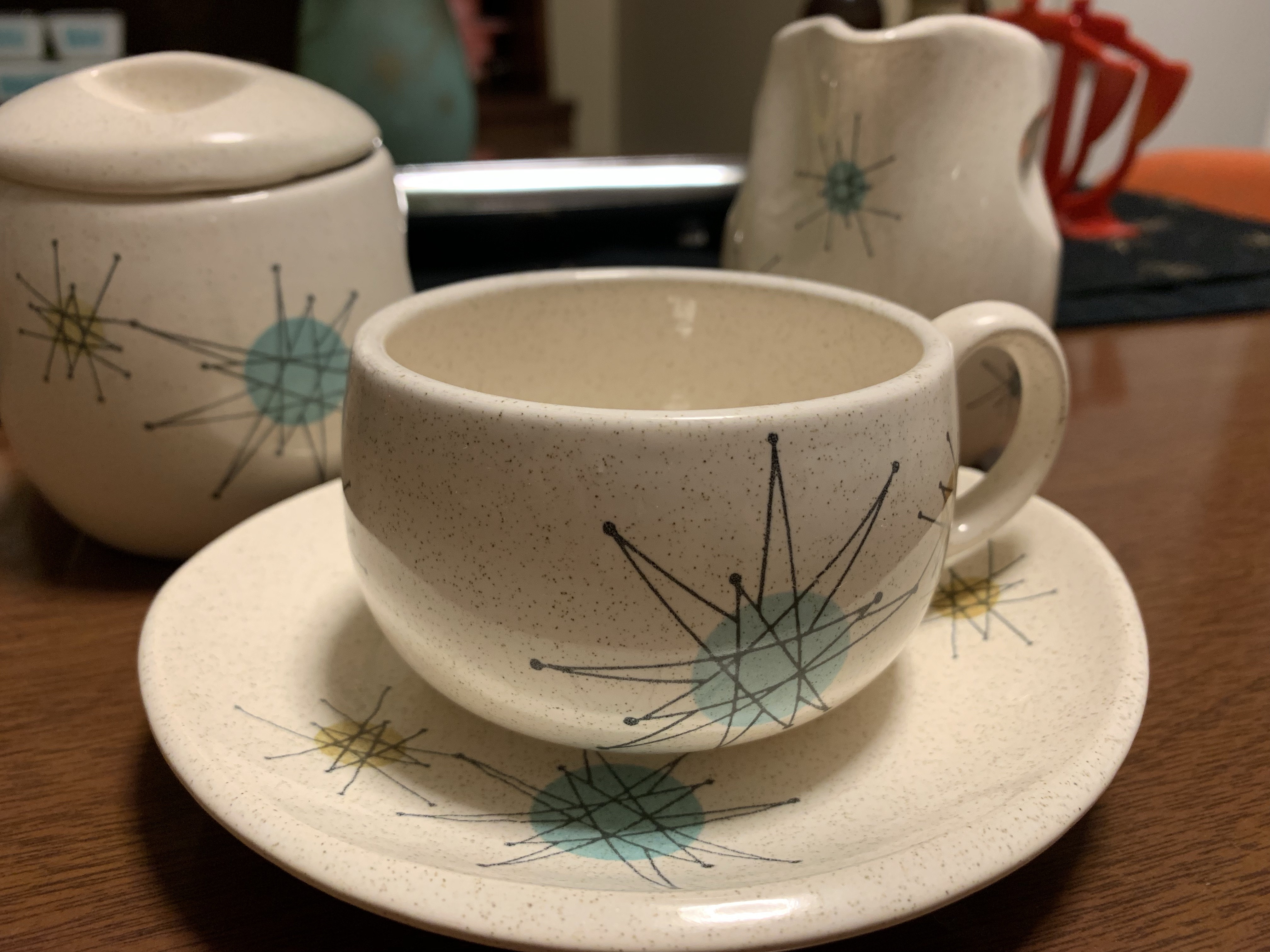 White cup and sauce with blue and black starburst pattern.