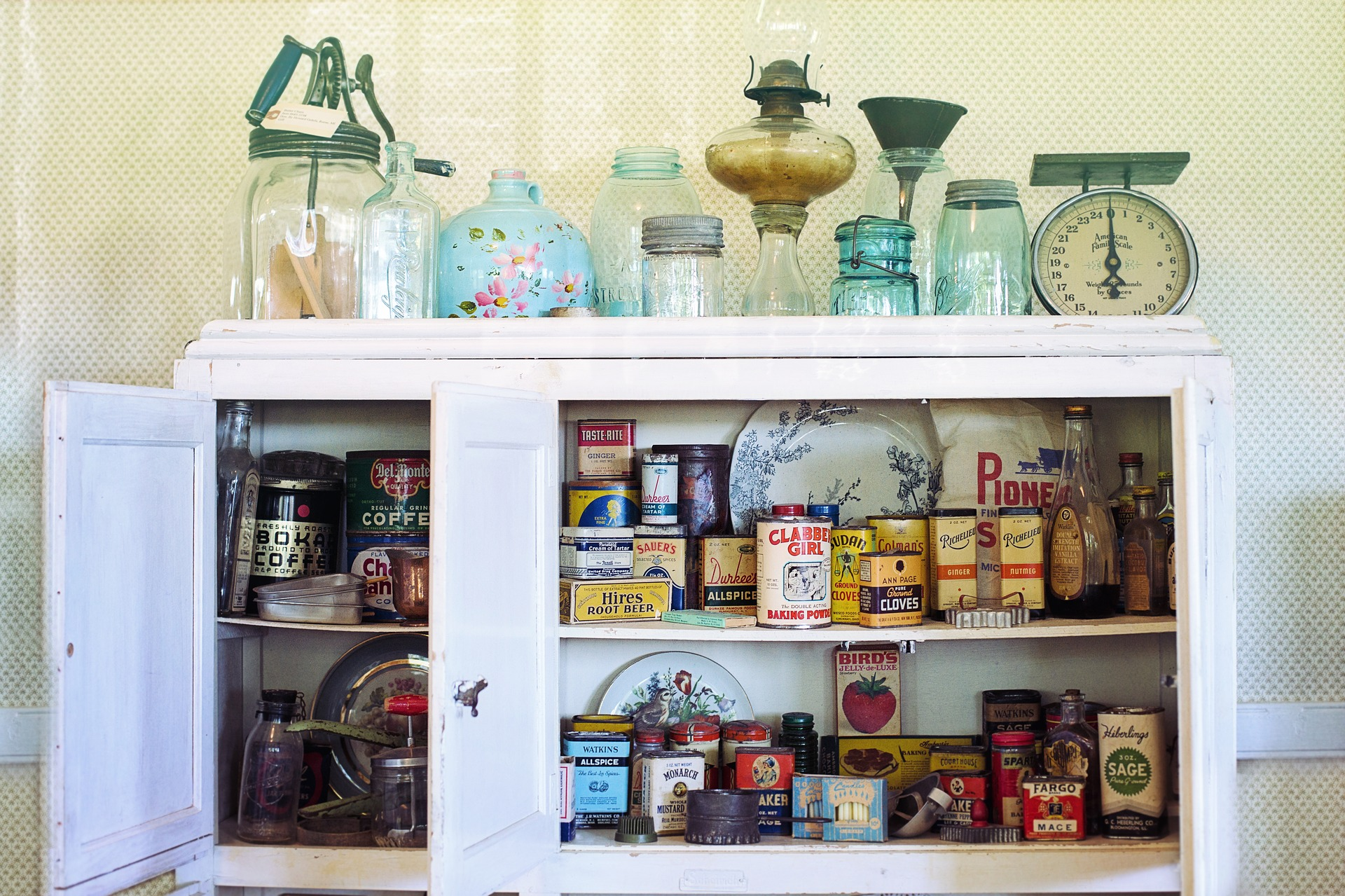 A cabinet with lots of old jars and cans.