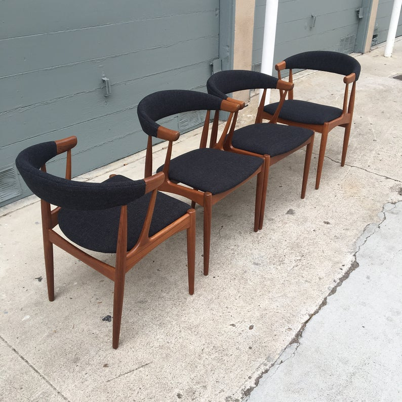 Four wooden chairs upholstered with dark fabric.