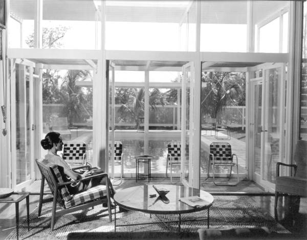 Black and white image of woman in glass sitting room.