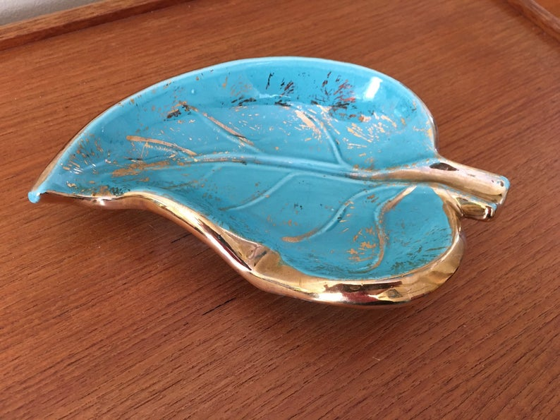 Blue and gold ashtray shaped like a leaf sitting on a wooden surface.