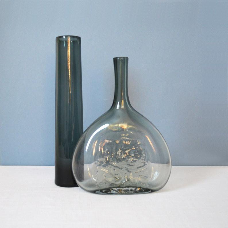 Two gray glass vases on a white counter with blue background.
