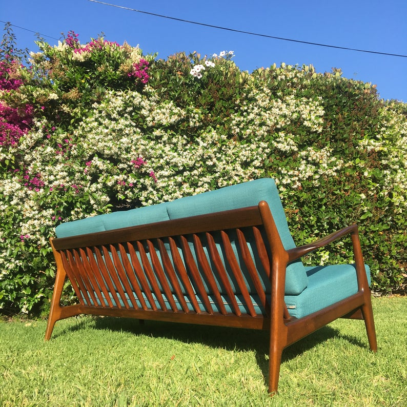 Back of wooden sofa with teal upholstery in a garden.