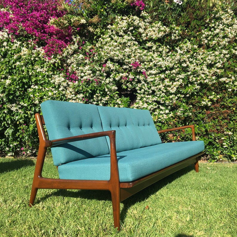 Wooden sofa with teal upholstery in a garden.