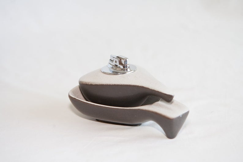 grey and white lighter nested in a matching ashtray.