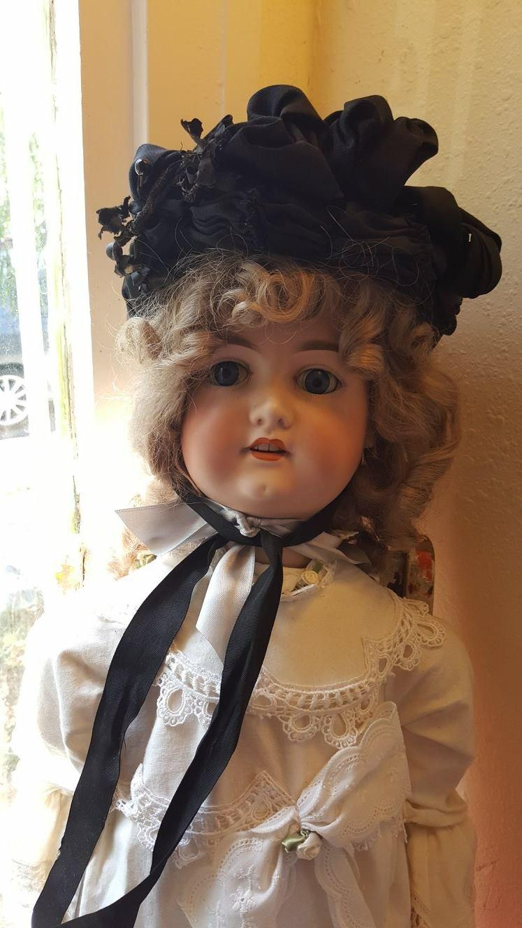 Victorian vintage porcelain doll displayed on stand